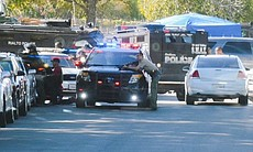 Law enforcement officers prepare to search buil...
