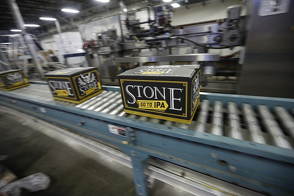 Workers brew, bottle and pack craft beer at Stone Brewery...