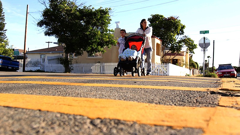 Krystal Ortega and her sons, Aaron and Aiden, walk to Adams Elementary School...
