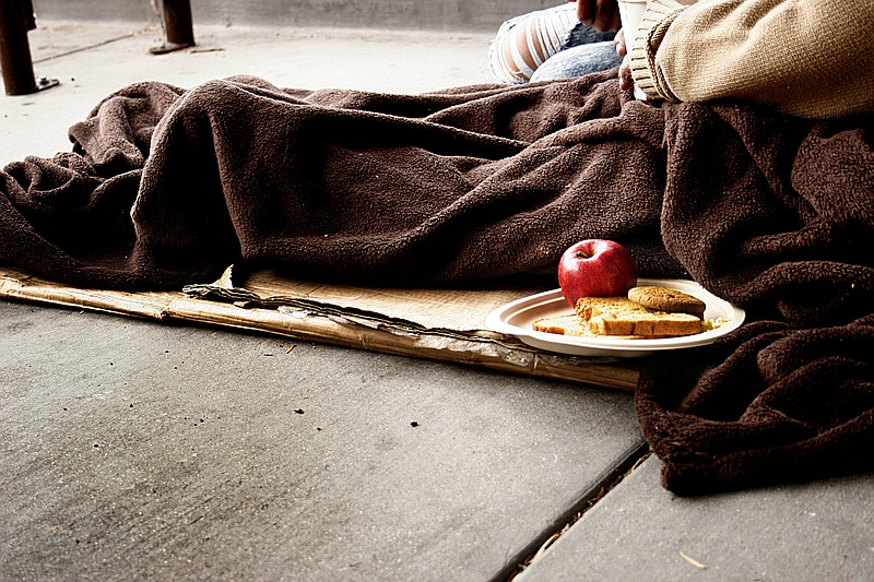 Susan Davis sits on layers of cardboard on a sidewalk in the City Heights nei...