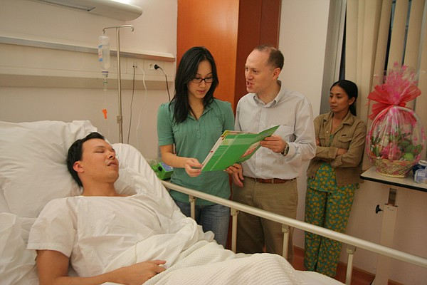 Hospital personnel discuss a patient's care at his bedsid...