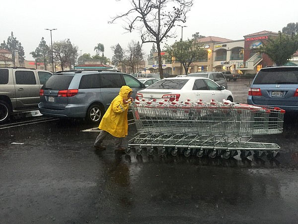 A man collects shopping carts in front of the H Mart in Mira Mesa as the rain...