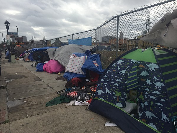 Dozens of people hunker down in tents on 16th Street in downtown San Diego aw...