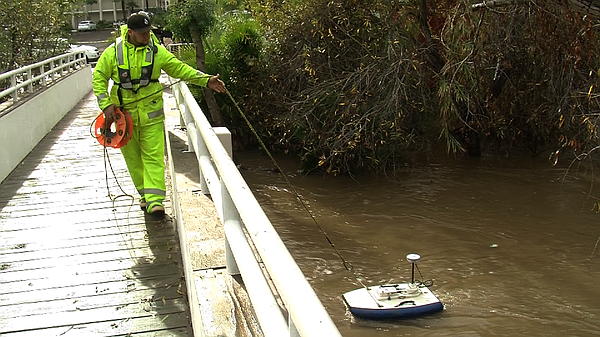 A USGS hydrologist collects San Diego River data using a ...
