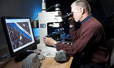 Robert Hazen studies thin slices of rock under ...