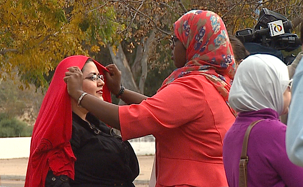 A woman helps adjust another woman's hijab at a rally in solidarity with Musl...