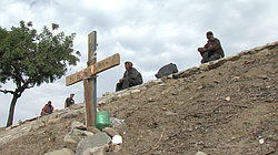 Migrants sit behind a memorial cross erected for a friend killed on the highw...