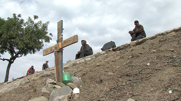 Migrants sit behind a memorial cross erected for a friend...