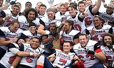 Group photo of football players celebrating a w...
