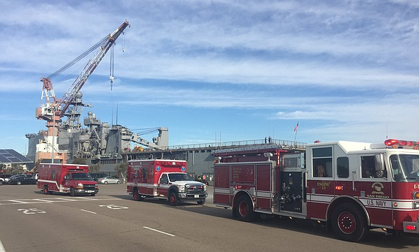 Emergency vehicles line up along a pier beside the USS Rushmore during a shoo...