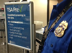 A TSA officer stands next to a sign for the Pre-Check program, Feb. 11, 2015.