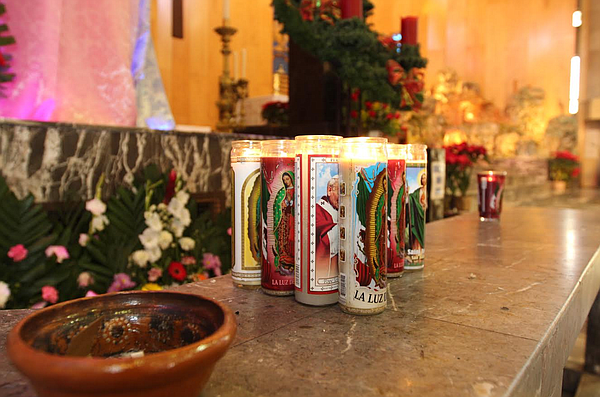 Visitors to the Cathedral of Our Lady of Guadalupe in Juárez place votive can...