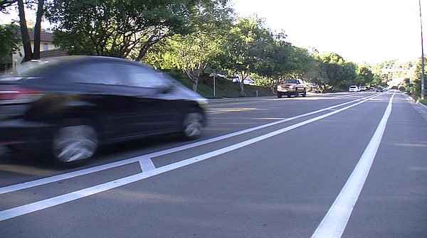 A car drives past a buffered bike lane on Collwood Boulev...