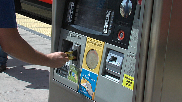 An MTS rider swipes his credit card at an MTS ticket machine in April 2013.