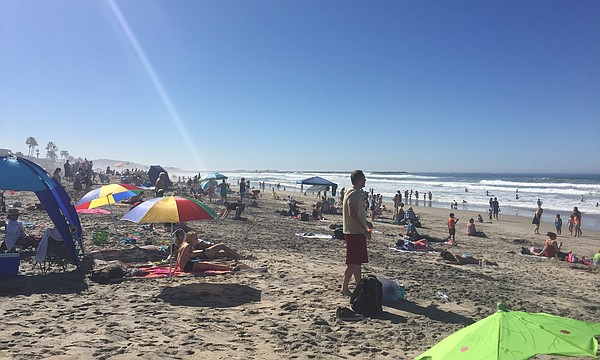 Hundreds of people — loaded with boogie boards, towels an...