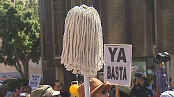 A protestor holds up a mop at a march to raise awareness about assault in the...