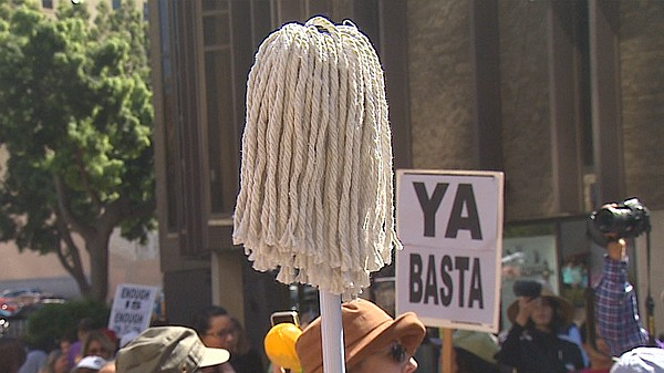 A protestor holds up a mop at a march to raise awareness ...
