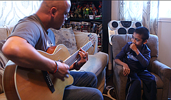 Damian Omler listens while his father Donnie plays guitar, Feb. 19, 2016.