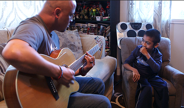 Damian Omler listens while his father Donnie plays guitar...