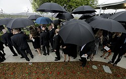 People wishing to pay their respects wait in the rain during the graveside se...