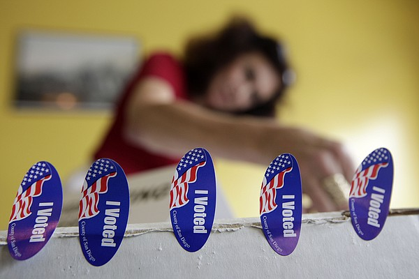 Poll worker Melanie Withey attaches
