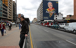 A clear bus lane beside traffic in downtown Bogotá. On the upper right, a mur...