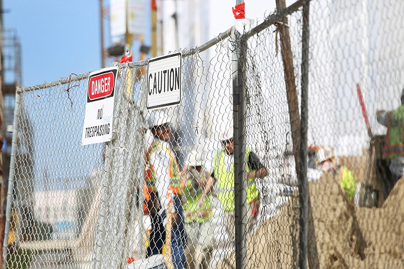 Danger and caution signs hang on a fence outside a construction site in San D...