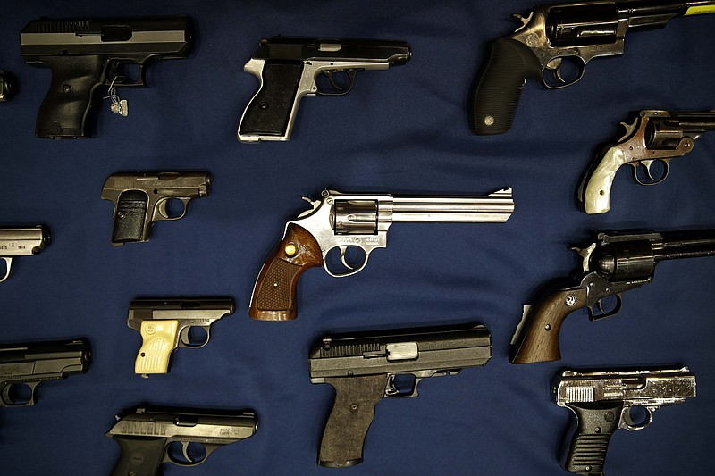 Guns seized by the police are displayed during a news conference, Oct. 27, 2015.