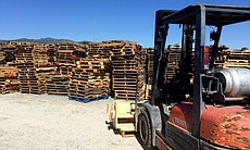 A forklift and several wood pallets are seen in...