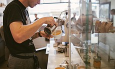 A barista pours cream at Revolution Roaster in ...