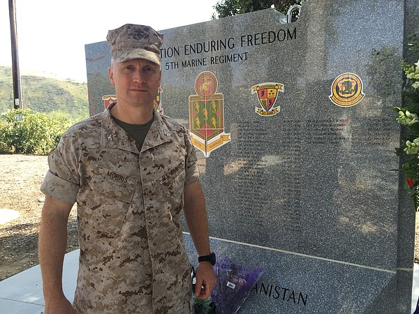 Col. Jason Morris stands by a memorial wall at Camp Pendl...