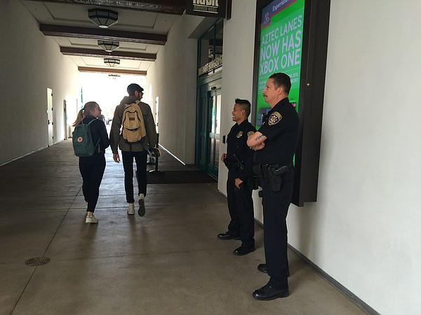 Two California State University police officers stand by ...