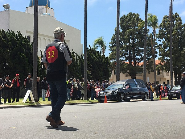 A man stands on a street in Coronado during a procession ...