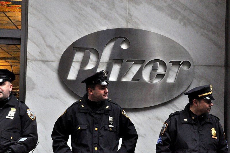 Police officers stand in front of Pfizer's New York City headquarters during ...