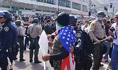 A man wearing an American flag on his back hold...