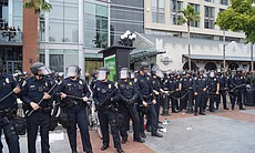 Several police officers wearing head gear hold ...