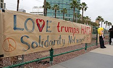 "A banner reads ""love trumps hate"" at Donald Tru..."
