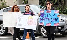 Anti-Trump protesters hold signs, May 27, 2016.