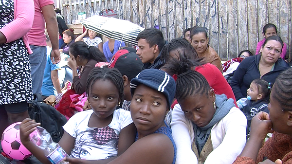 Migrants from Haiti and Africa wait outside the San Ysidr...