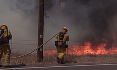 Firefighters battle a rapid moving wildfire nea...