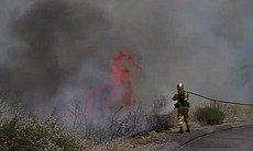A firefighter works to extinguish flames near t...