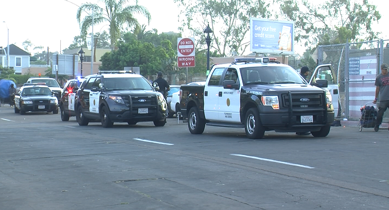 San Diego police cars with flashing lights roll...