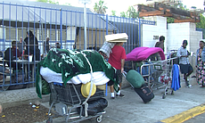 Homeless people wheel their overloaded carts to...