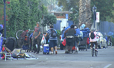 Homeless people push their carts on 17th Street...