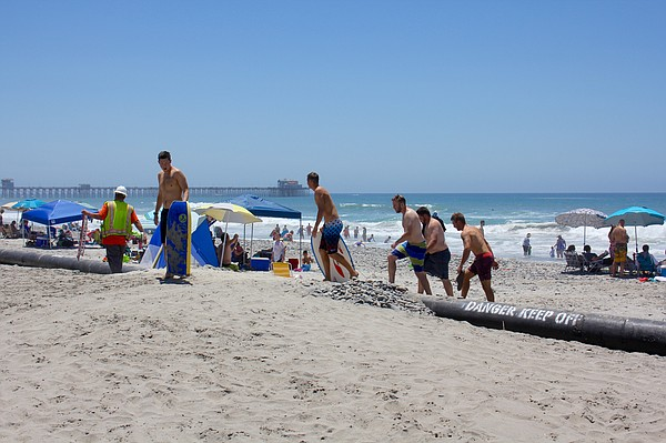 Beachgoers use an access ramp to cross dredge pipes at an...