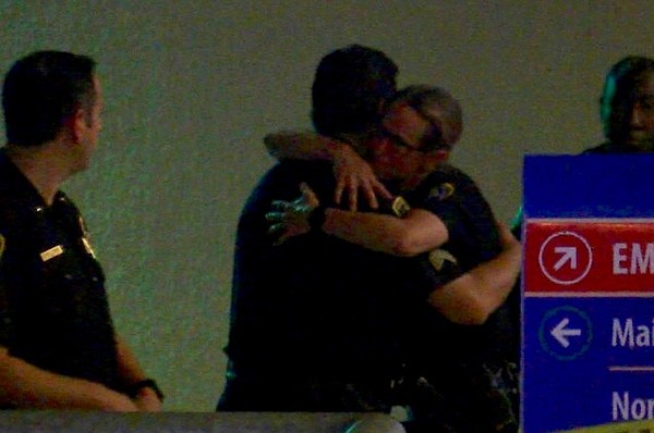 San Diego police embrace outside Scripps Mercy Hospital i...