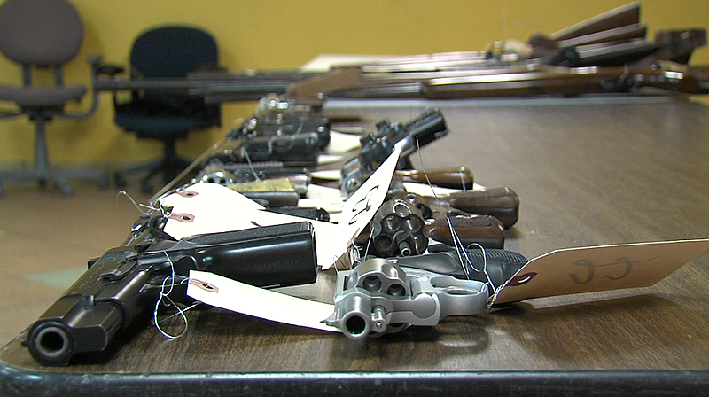 Guns sit on a table after being turned in to San Diego police at a gun buybac...