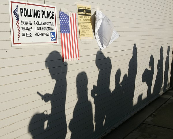 The rising sun casts shadows of voters waiting to vote at...