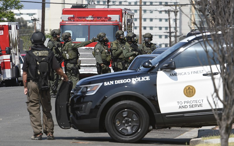 San Diego Police SWAT officers surround a house with a possible suspect insid...