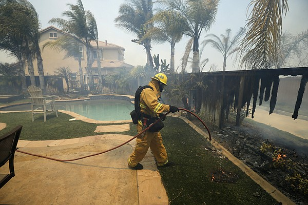 A firefighter puts water on a house fence during a wildfi...